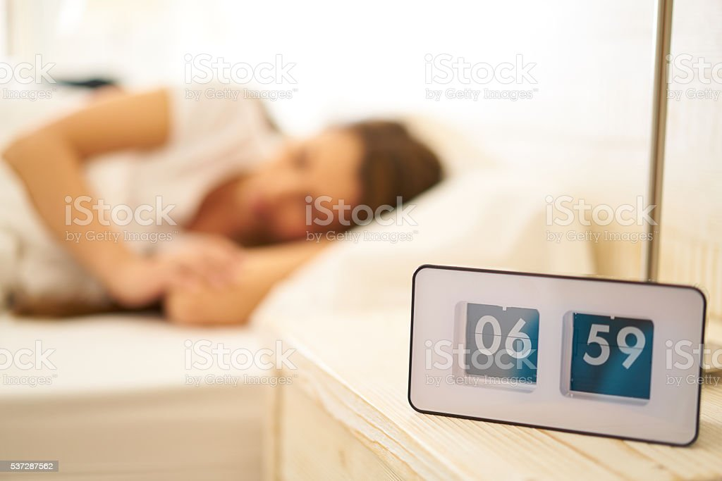vintage clock with sleeping woman before wakeup call stock photo
