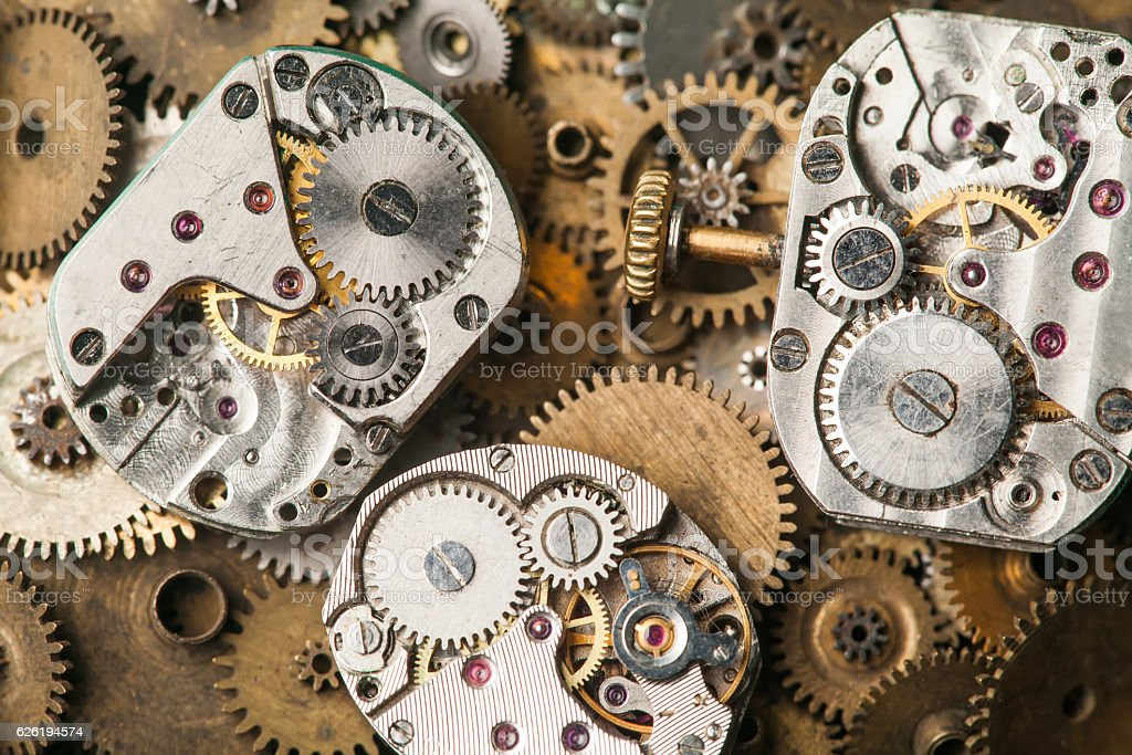 Vintage clocks mechanism close-up. Aged hand watches parts on stock photo
