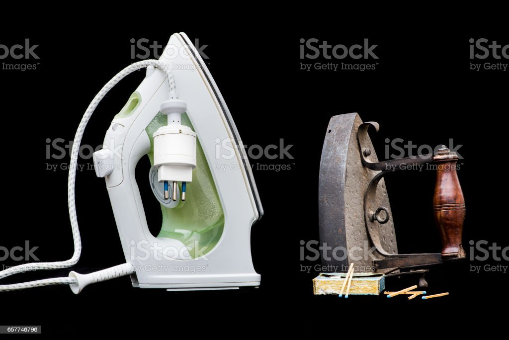 Vintage coal flat iron and modern steam iron. Concept of progress, contrast new old, evolution, development, well being, change, improvement stock photo