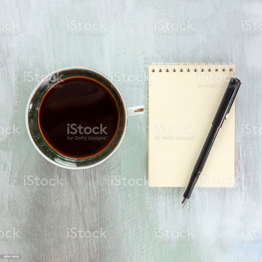 Vintage coffee cup with ink pen on notepad stock photo