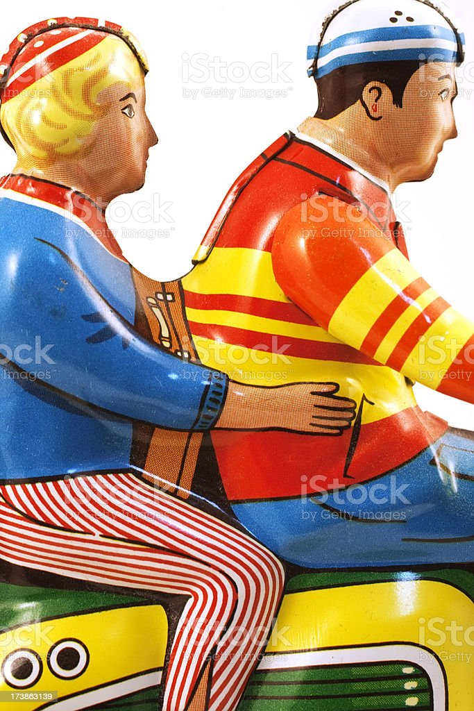 Vintage colorful tin toy scooter with rider and passanger. stock photo