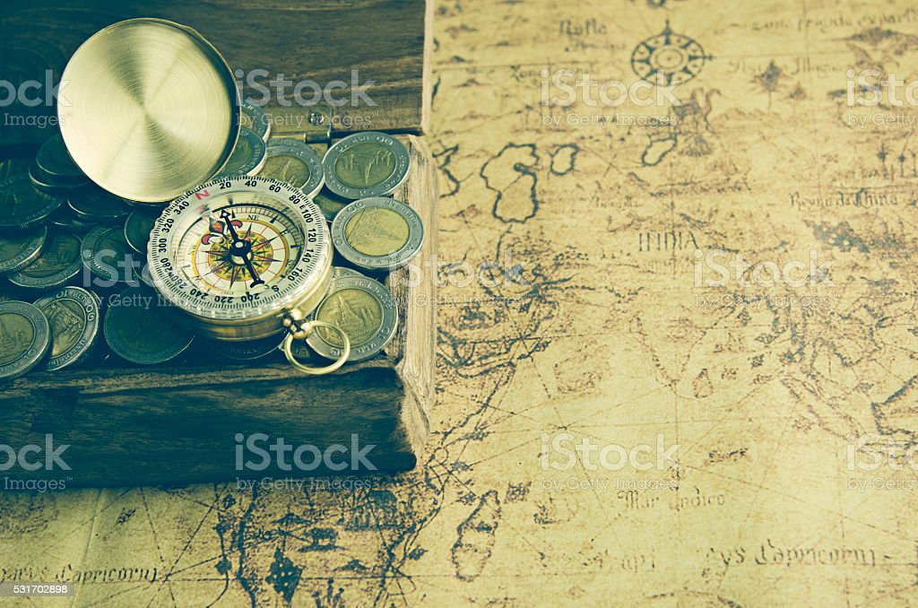 Vintage compass and coins on old map stock photo
