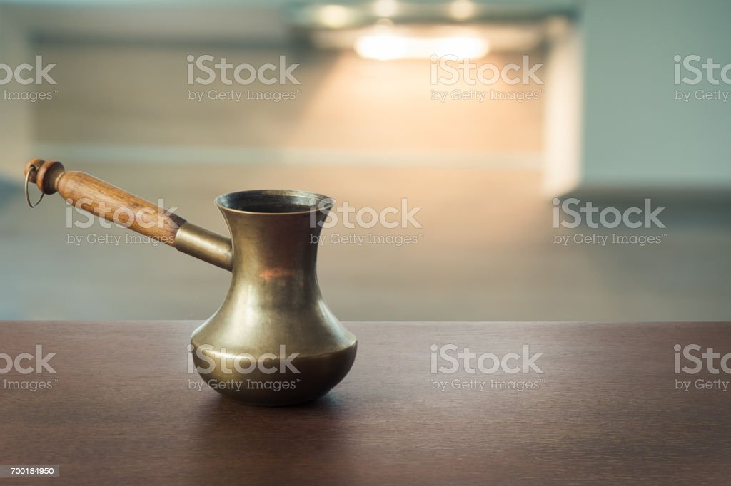 Vintage copper cezve with black coffee on wooden tabletop and defocused modern kitchen as background for display or montage your coffee products. stock photo