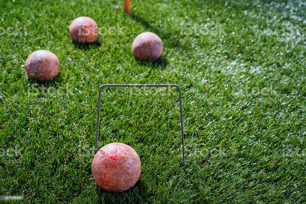 Vintage Croquet ball resting against a wire wicket stock photo