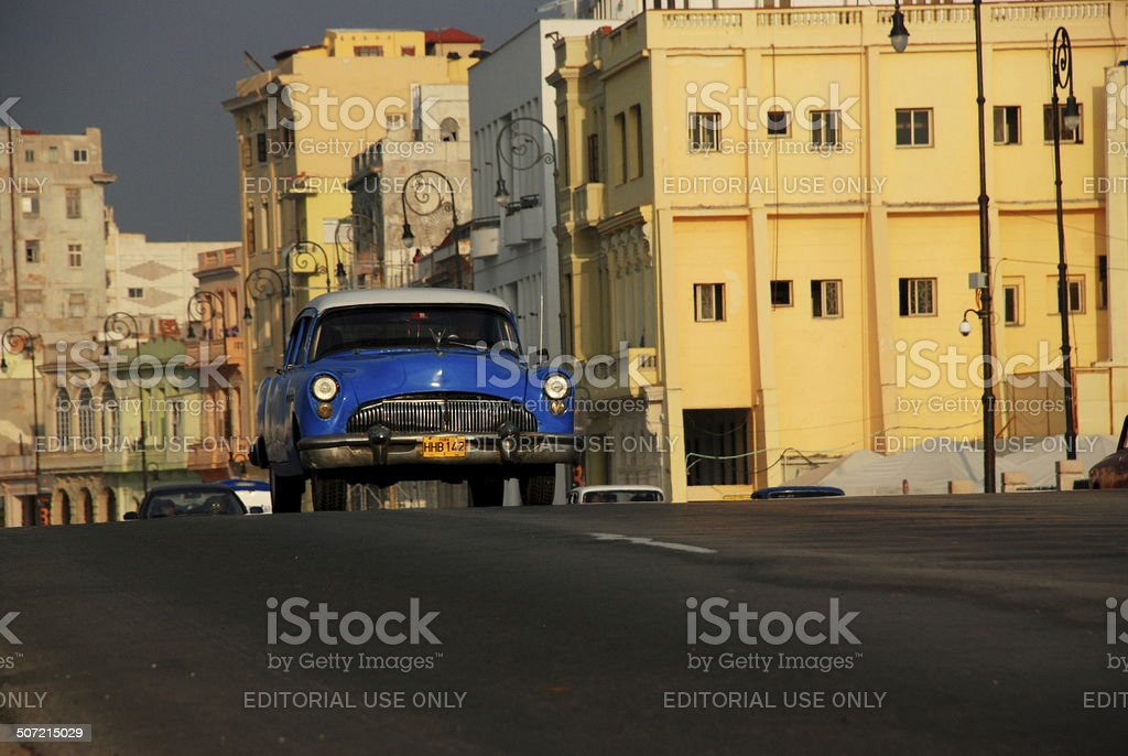 Vintage Cuban car drives over incline along Havana's Malecon stock photo