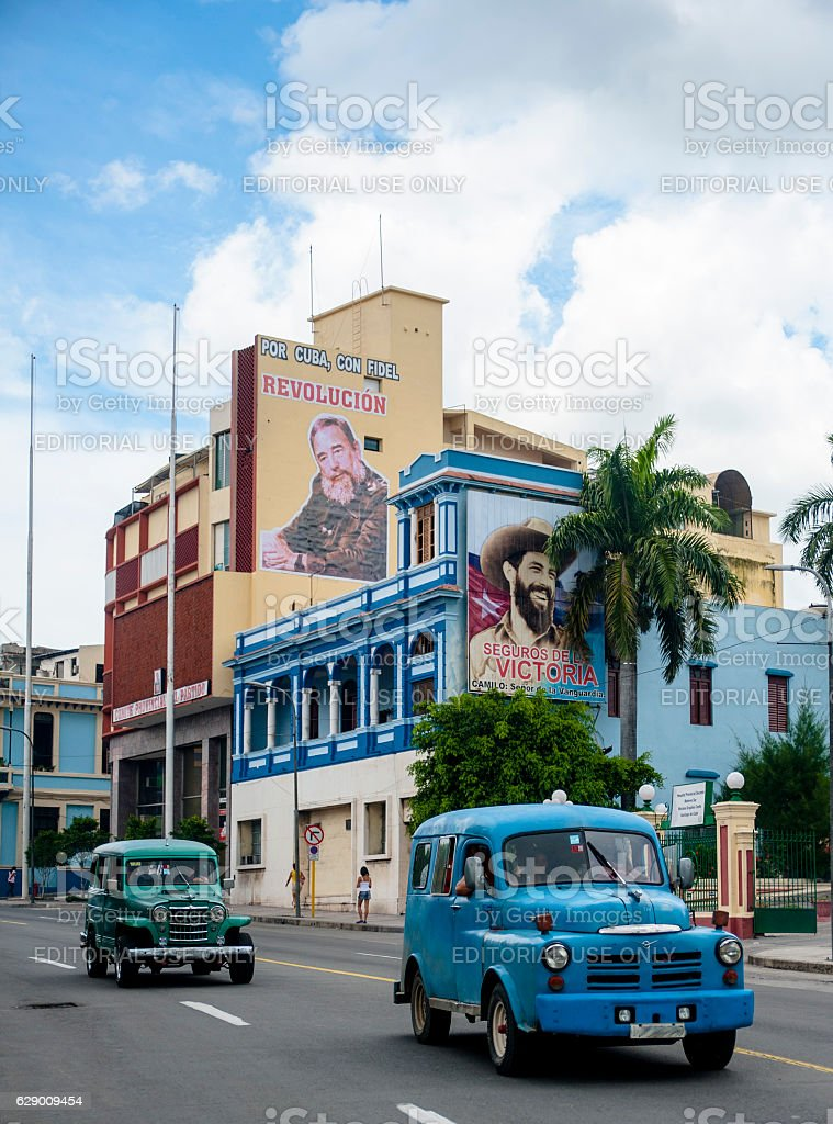 Vintage Cuban cars drive in front of Fidel Castro mural stock photo