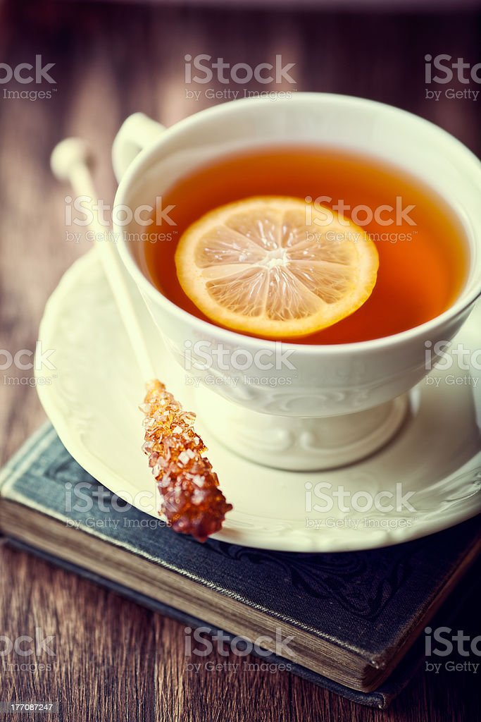 Vintage cup of Tea with Lemon on a Old Book stock photo