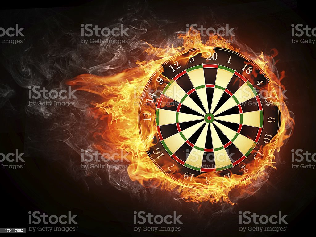 A vintage darts board smothered in flames stock photo