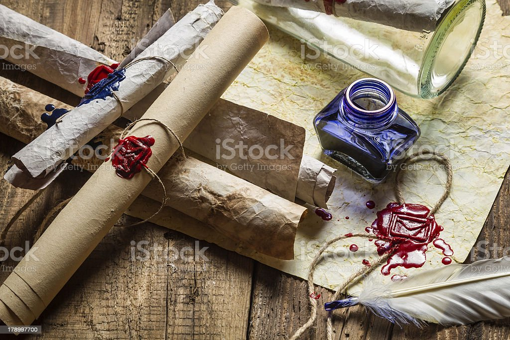 Vintage desk full of old scrolls scribe and blue ink royalty-free stock photo