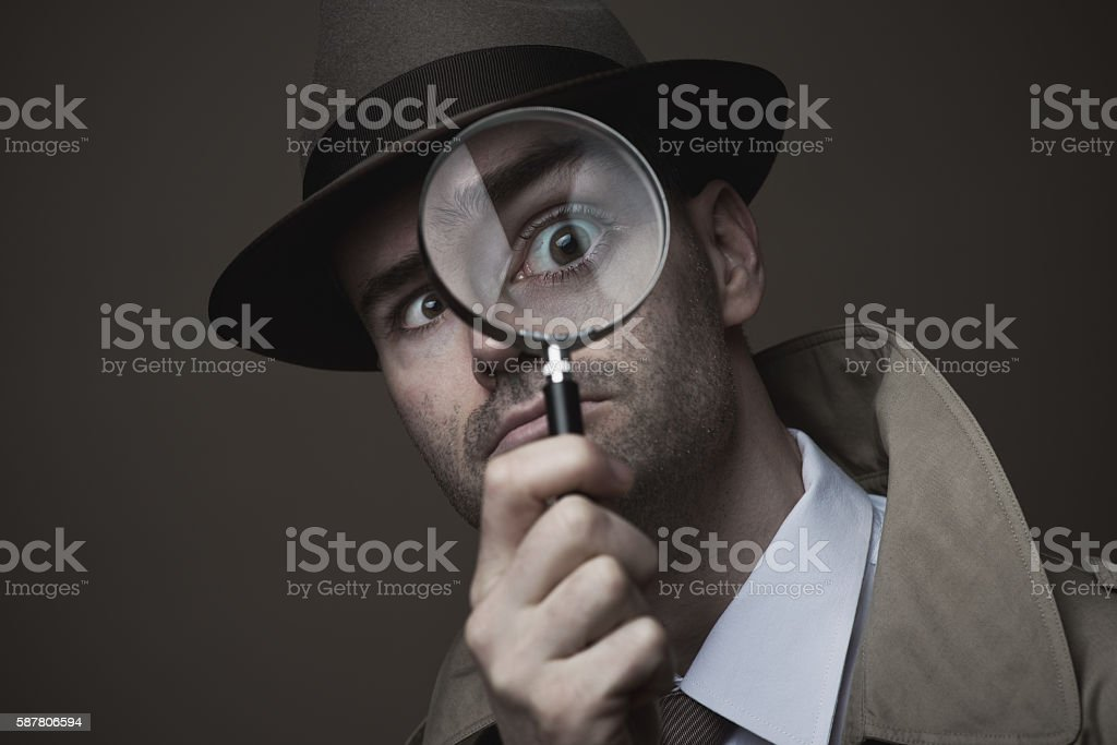 Vintage detective looking through a magnifier stock photo