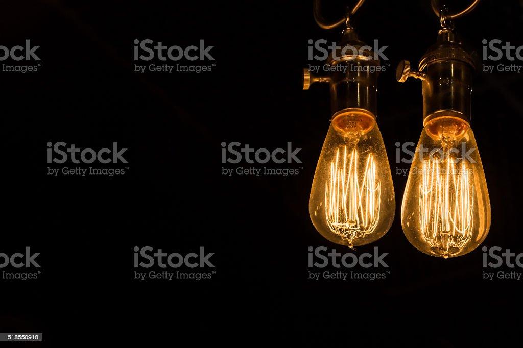 Vintage Edison Light Bulbs hanging against a black background stock photo