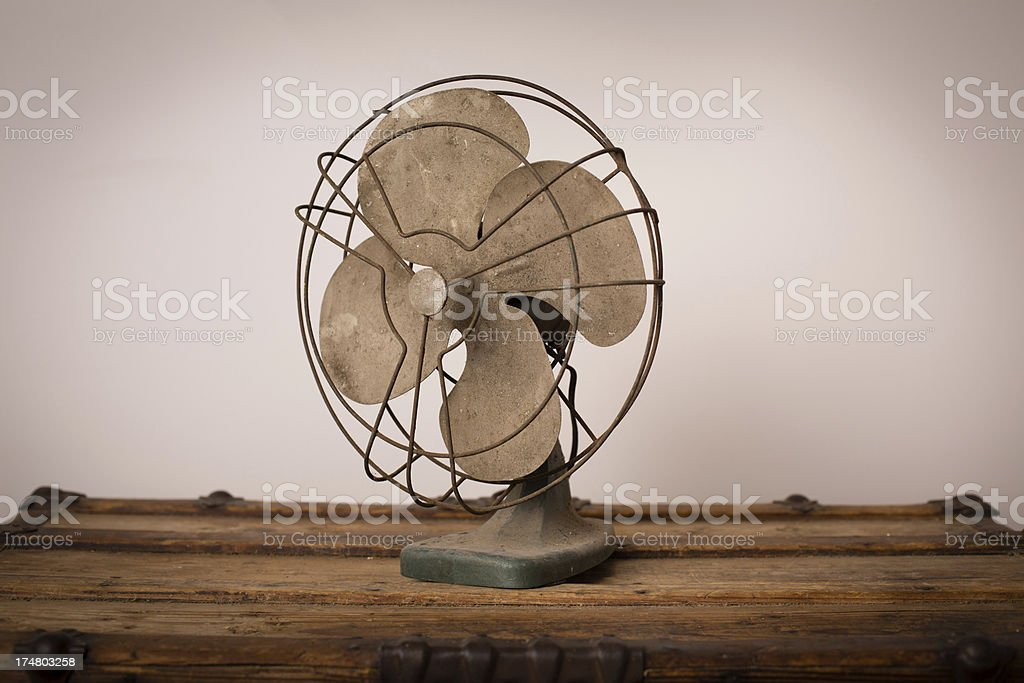 Vintage Electric Fan Sitting on Old Wood Trunk royalty-free stock photo