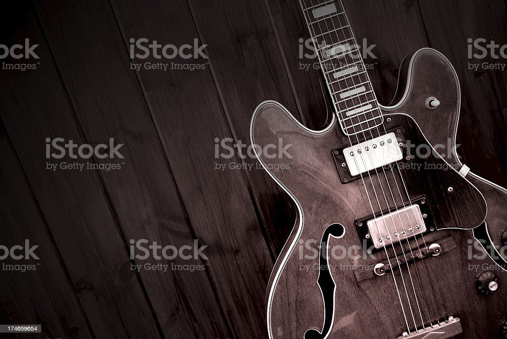 A vintage electric guitar lying on a wooden floor. stock photo