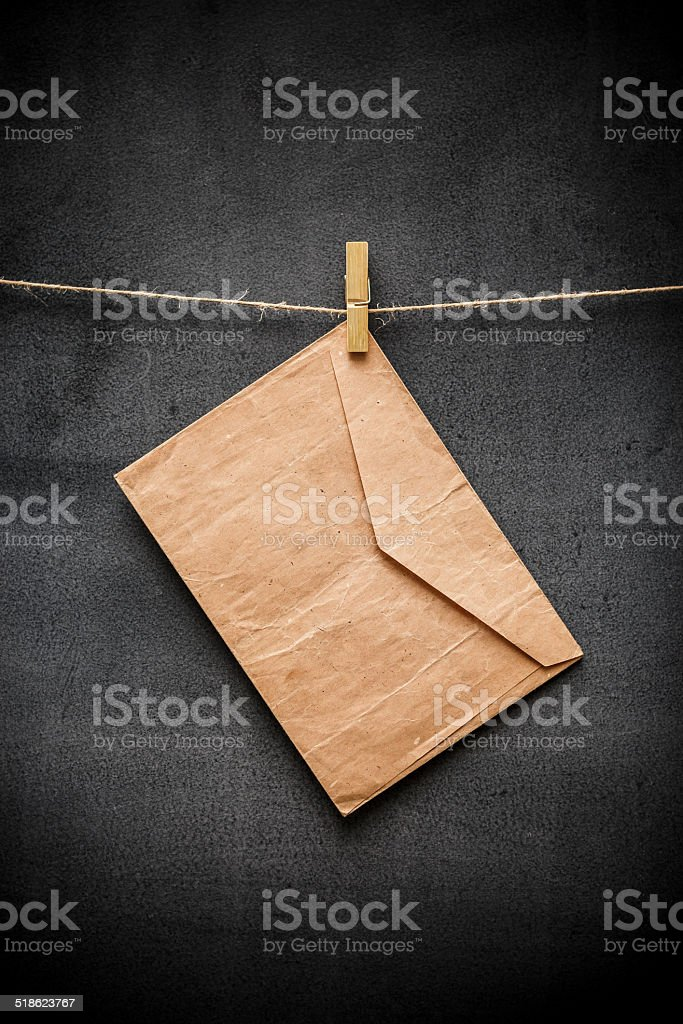 Vintage envelope on clothes rope with black background stock photo
