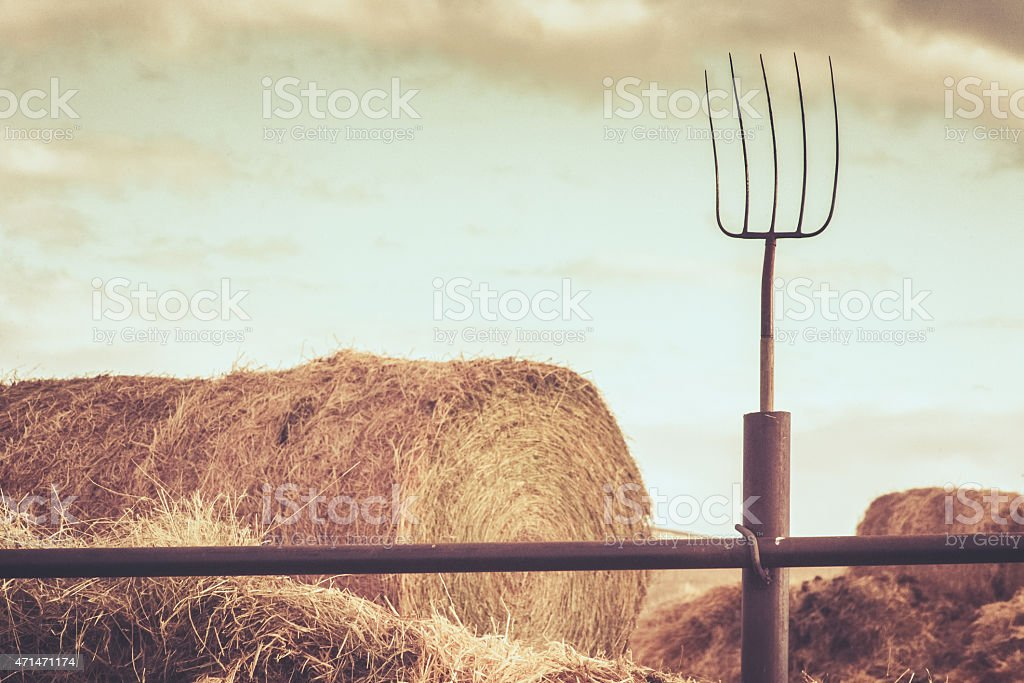 Vintage farm scene - Fenced in haystack, pitchfork  and sky stock photo