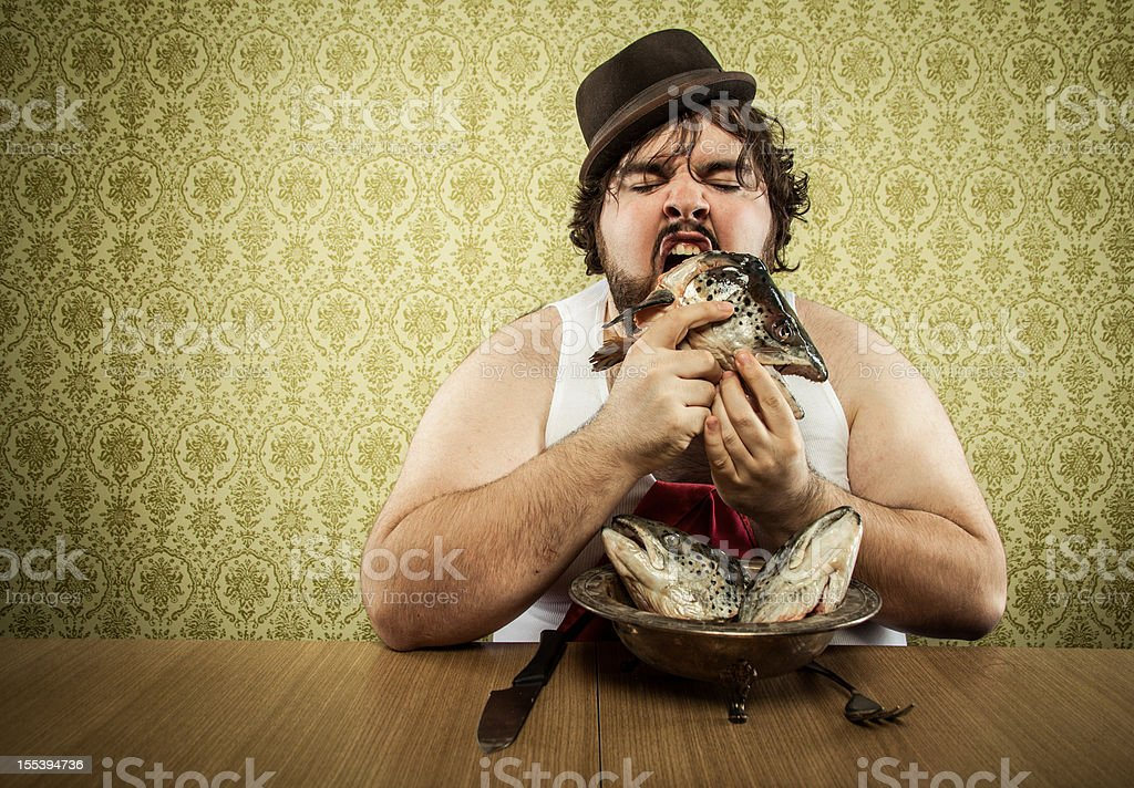 vintage fat man eating fish head soup at wood table stock photo