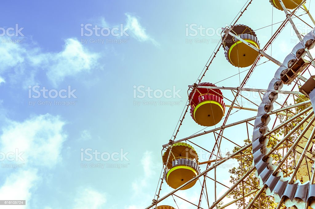 Vintage ferris wheel on the blue sky with clouds stock photo