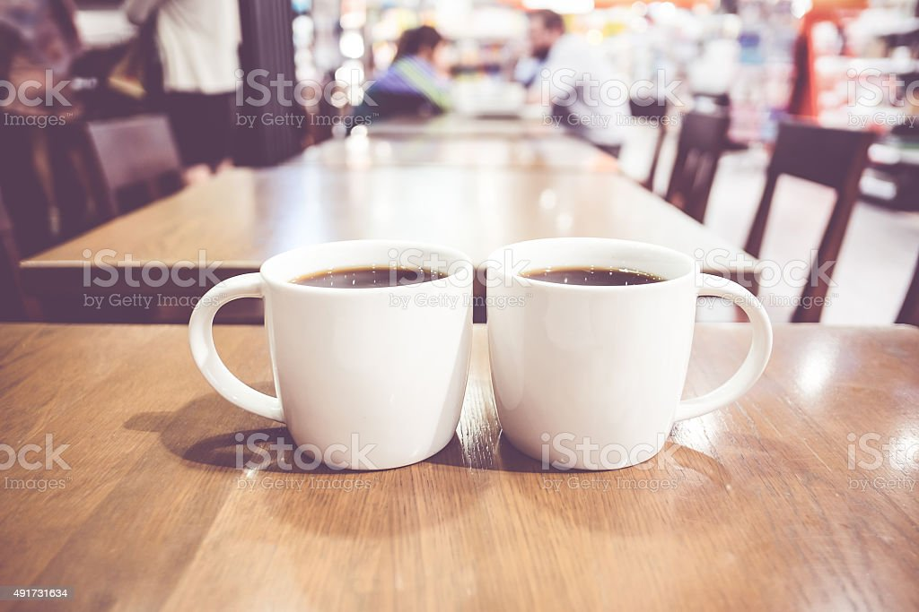 Vintage filter, couple of White coffee cup on wood table stock photo