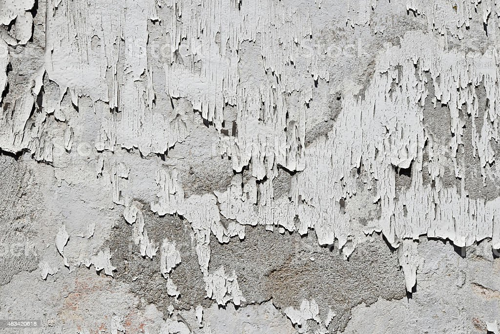 Vintage flakes of old white paint over grey concrete wall royalty-free stock photo