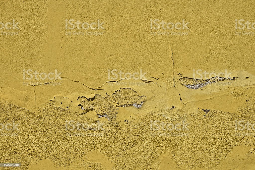 Vintage flakes of old yellow paint over grey concrete wall royalty-free stock photo