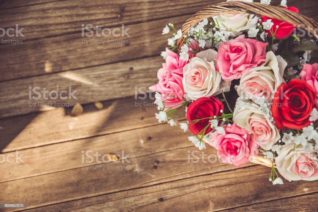 vintage flower rose in the basket on old wood background. stock photo