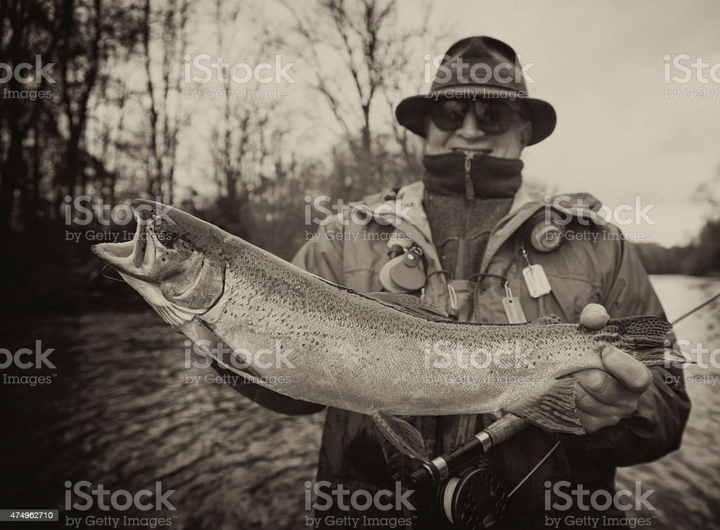 Vintage  Flyfishing - old Flyfisher with Trout stock photo