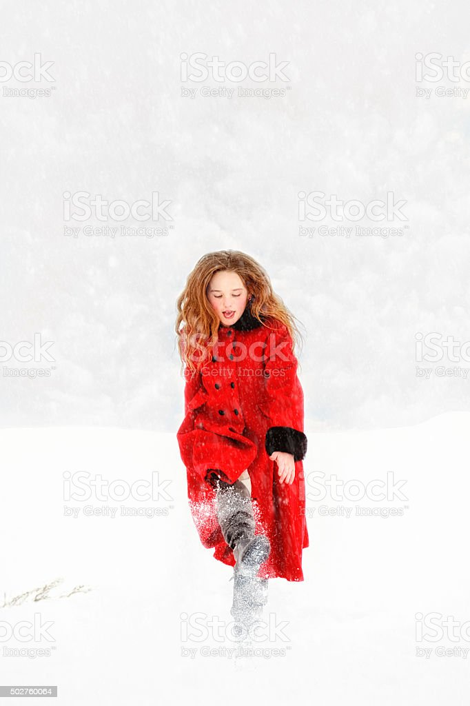 Vintage Girl In Red Coat Playing In A Snow Storm stock photo