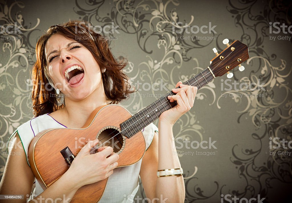 vintage girl sings and play ukulele on tapestry background stock photo
