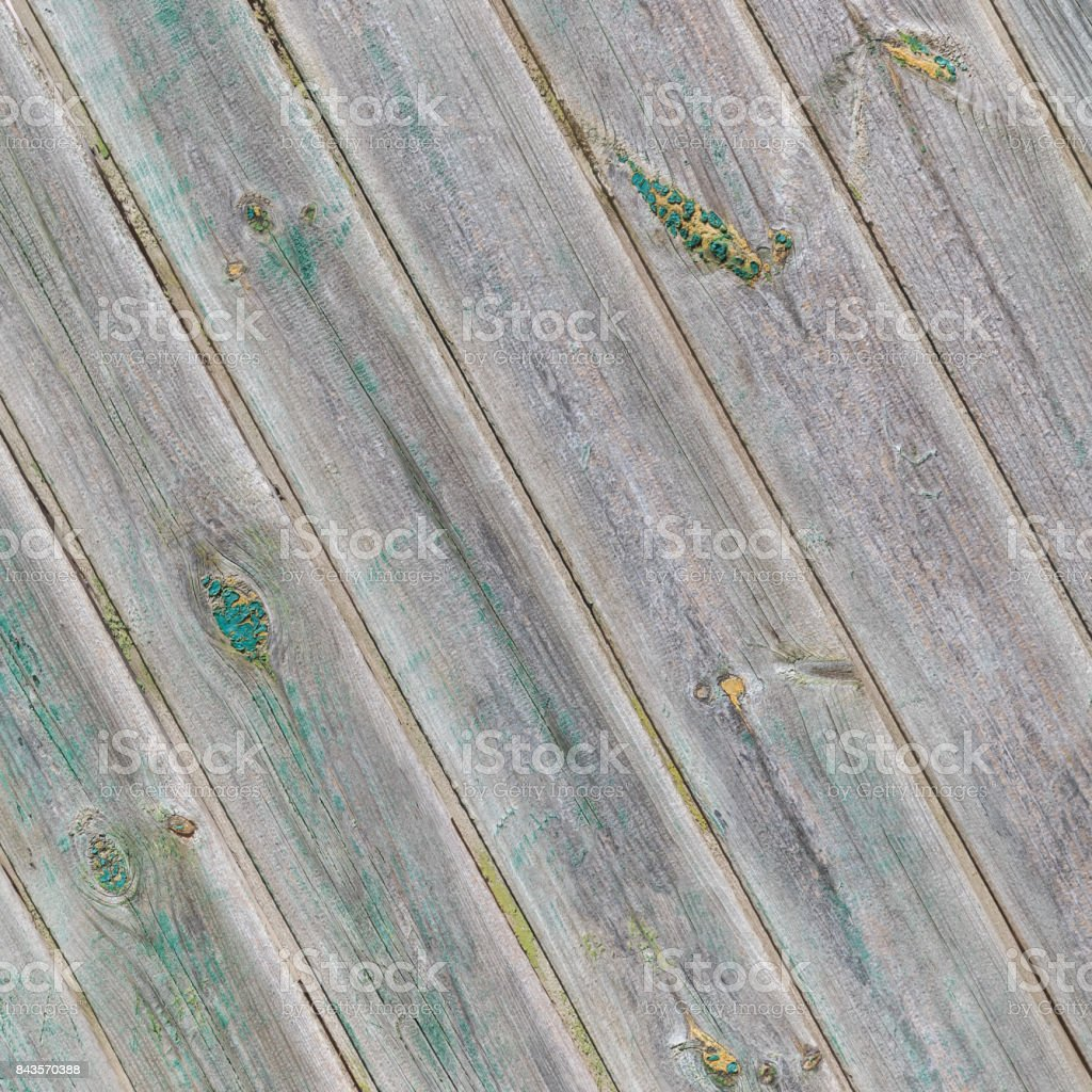 Vintage gray diagonal wooden boards with the remains of the green paint stock photo