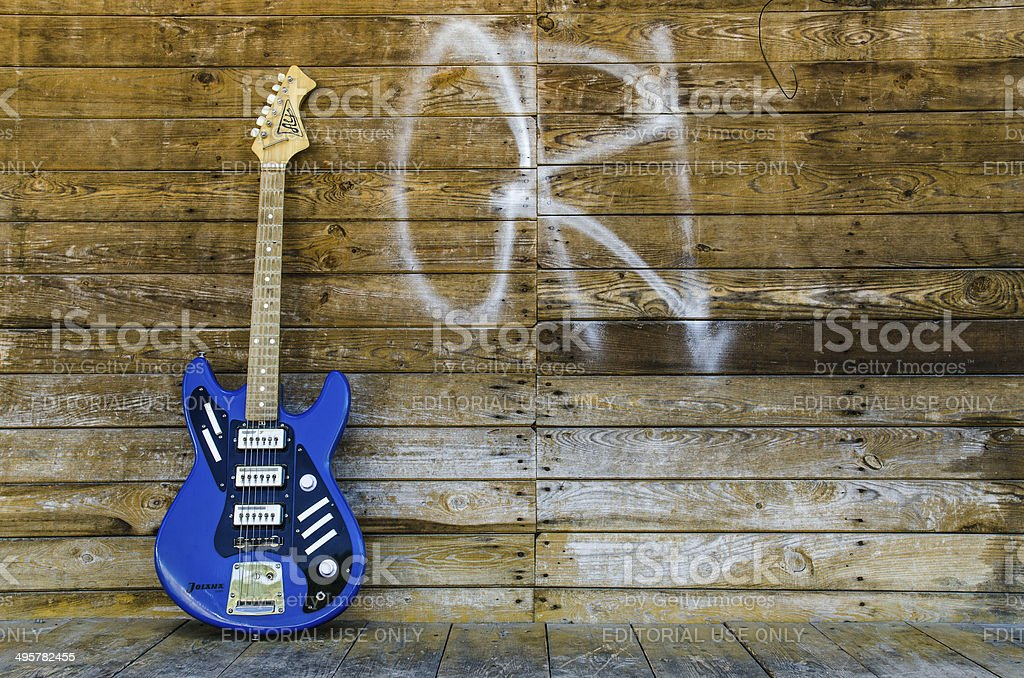 Vintage guitar from 1965 on wood background stock photo