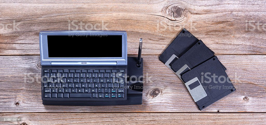 Vintage handheld computer and data disks on rustic wooden boards stock photo