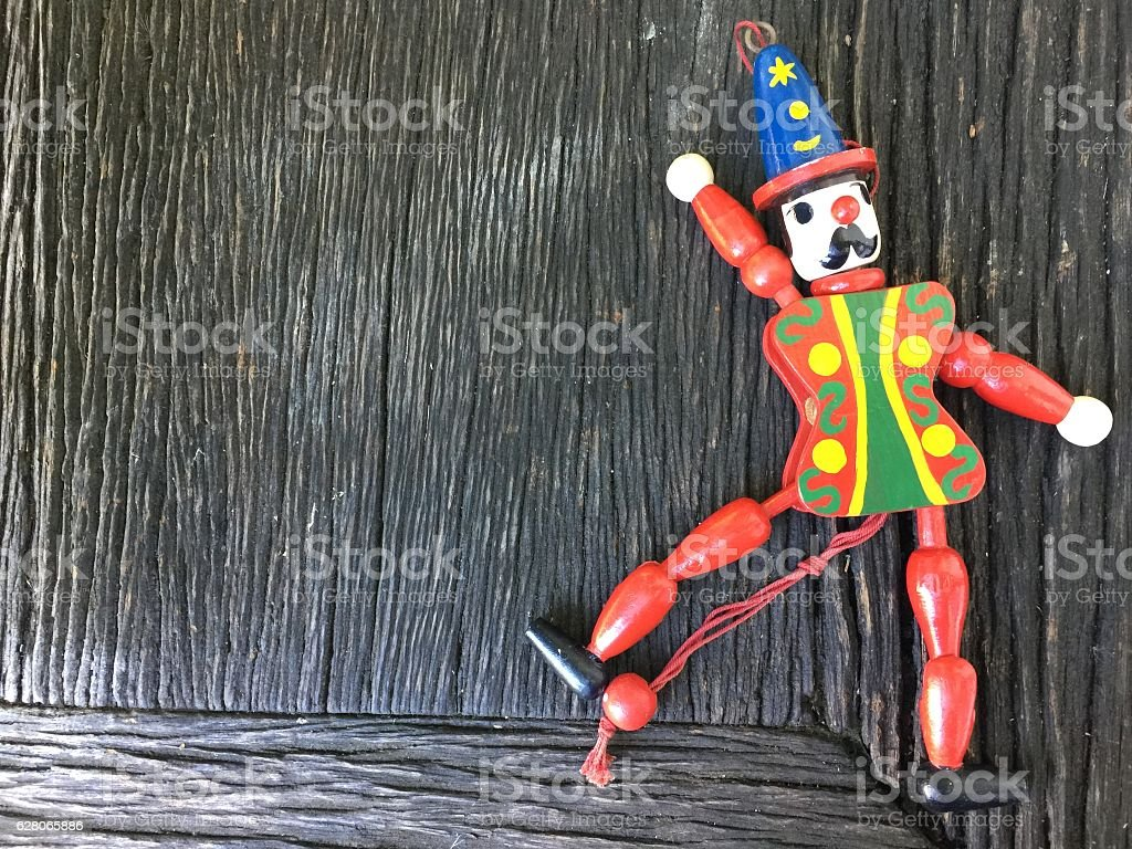Vintage Harleqin crown wood doll toy on wooden background stock photo