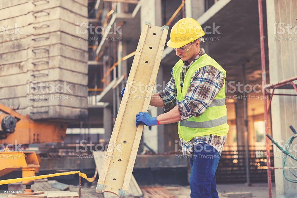 Vintage image of sweating construction worker with support planks stock photo