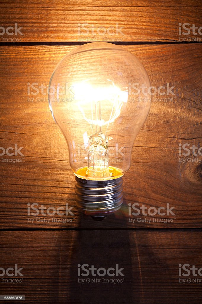 Vintage incandescent bulb on old wooden table stock photo
