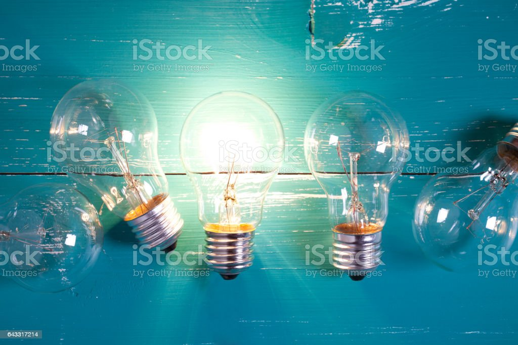 Vintage incandescent bulbs on turquoise wooden table stock photo