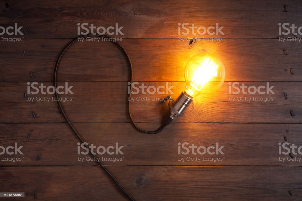 Vintage incandescent Edison type bulb on old wooden table stock photo