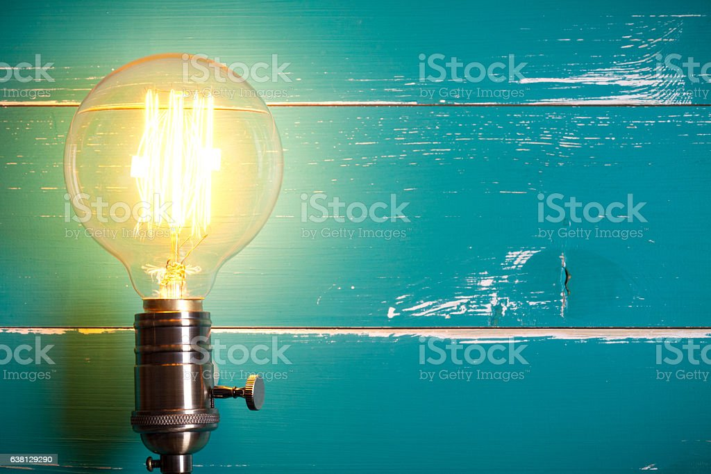 Vintage incandescent Edison type bulb on turquoise wooden table stock photo