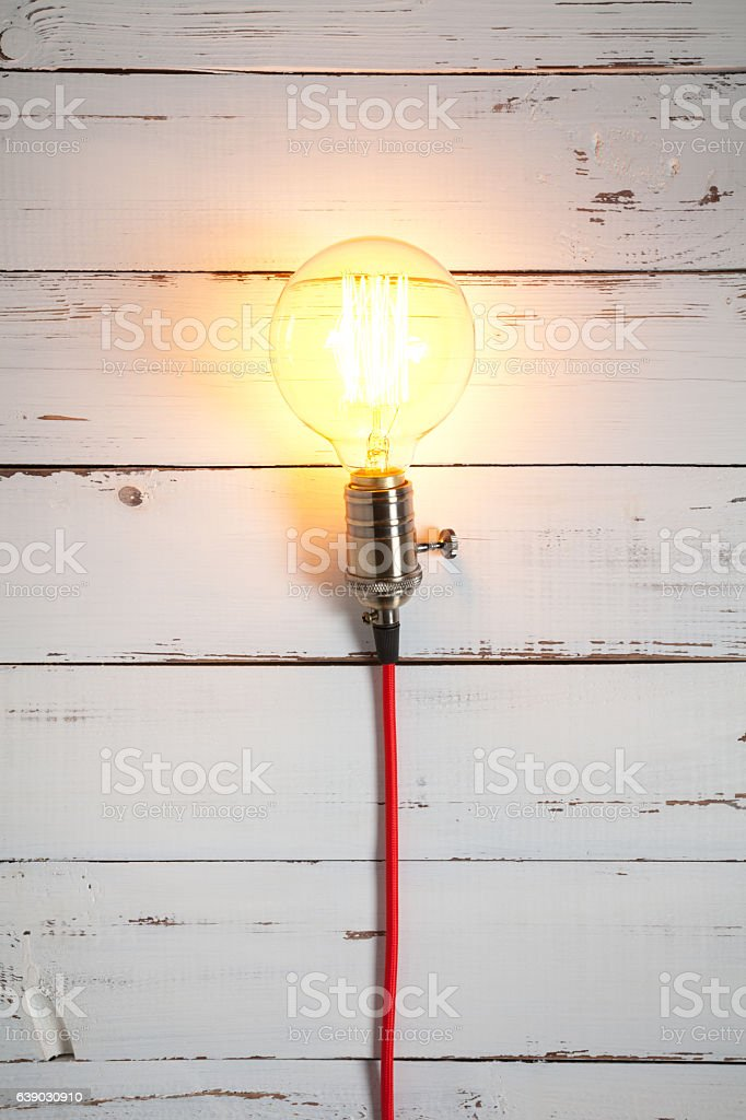 Vintage incandescent Edison type bulb on white wooden table stock photo