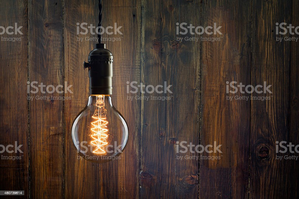 Vintage incandescent Edison type bulb on wooden background stock photo