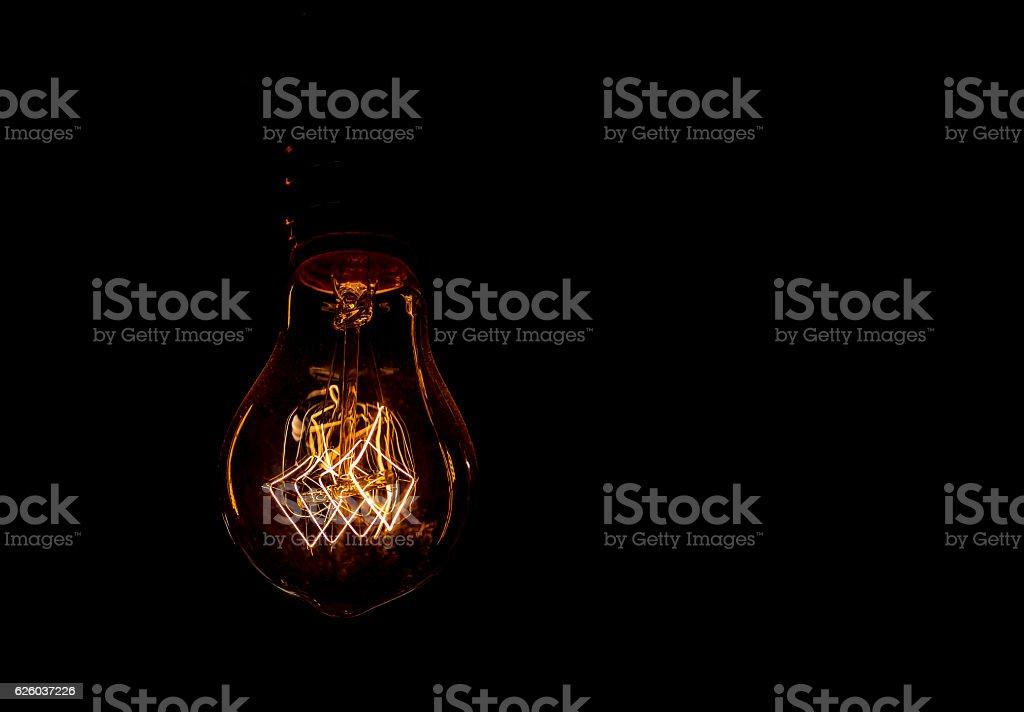 Vintage incandescent light bulb filament on black, close up shot stock photo