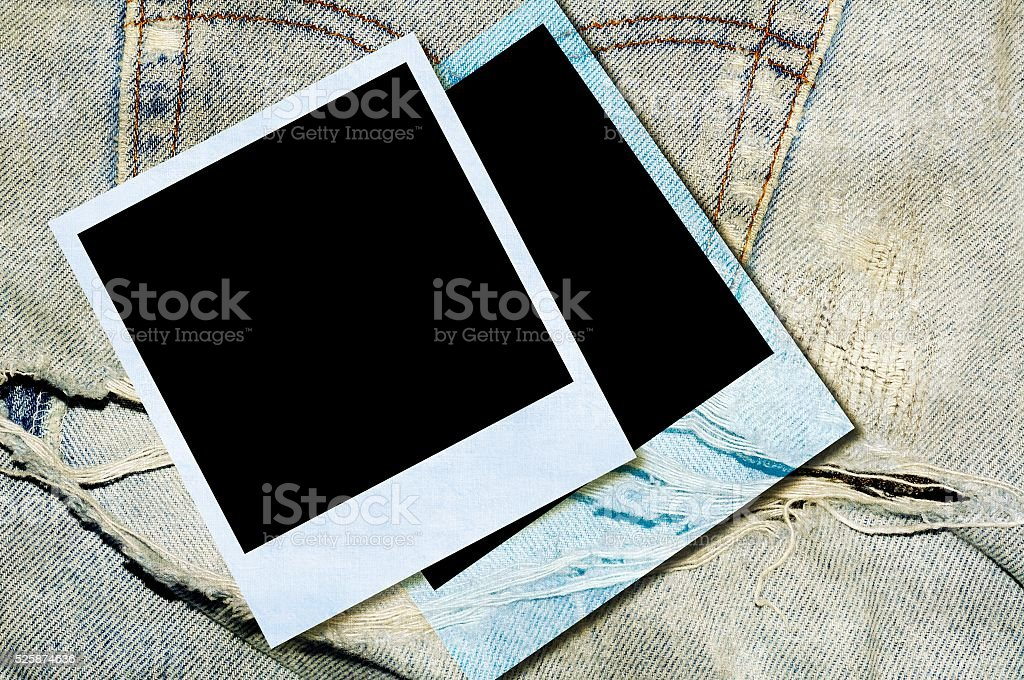 Vintage instant photos on torn and tattered blue jeans stock photo
