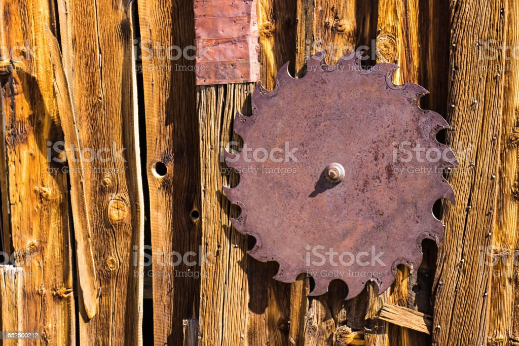 Vintage Iron Saw Blade on Side of 1800s Building stock photo