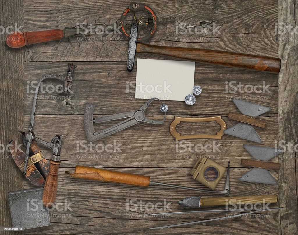 vintage jeweler tools and diamonds over wooden bench, blank card for...