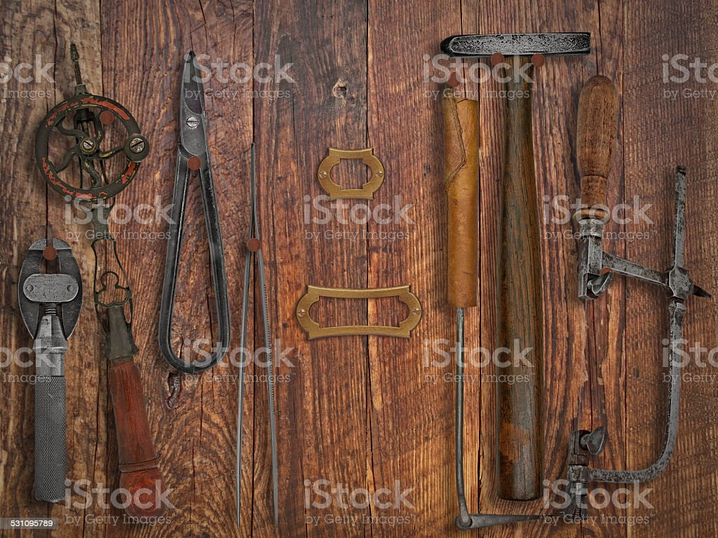 vintage jeweler tools over wooden wall stock photo