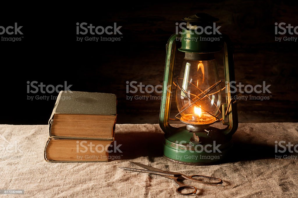 Vintage kerosene lamp and antique books on the linen tablecloth. stock photo