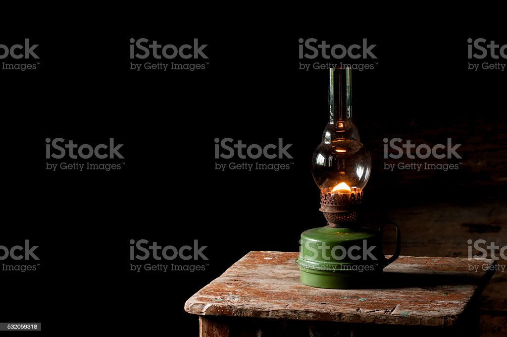 vintage kerosene lamp on the wooden stool stock photo
