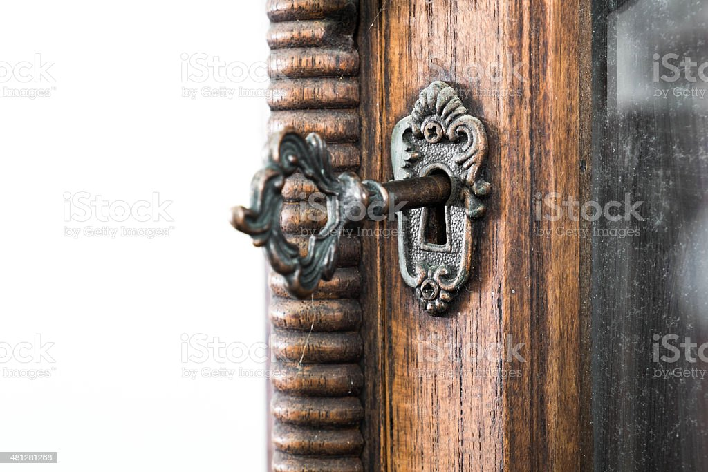 Vintage keyhole with key on vintage wooden cabinet stock photo