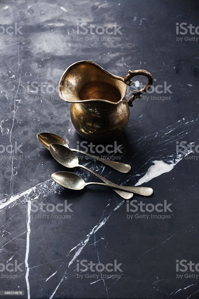 Vintage Kitchenware Silver milk jug and teaspoons stock photo