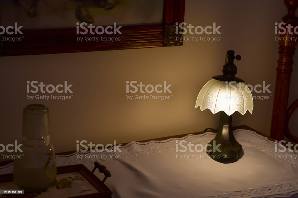 Vintage lamp on a desk, painting on the wall stock photo