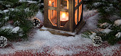 Vintage lantern with burning candle on snow covered wood